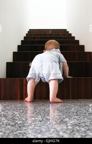 Baby boy climbing wooden stairs - Stock Photo