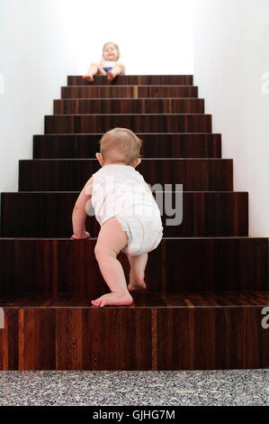Baby boy climbing wooden stairs, sister sitting at top - Stock Photo