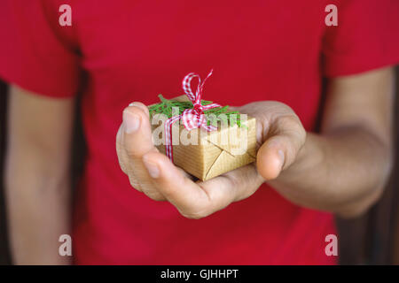 Man holding christmas gift in his hand - Stock Photo