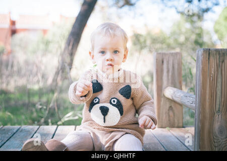 Boy sitting on built structure in playground - Stock Photo