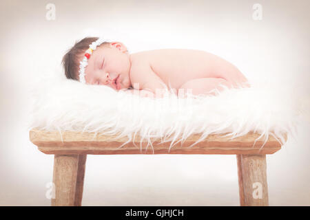 Portrait of a newborn baby girl sleeping on fluffy rug - Stock Photo