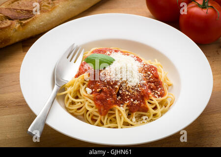 Spaghetti with marinara in a white bowl on a wood surface - Stock Photo
