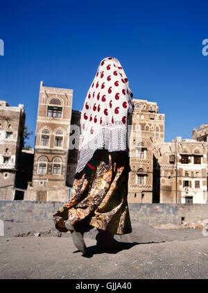 Sana'a, Yemen-February 12, 2012: A veiled Muslim woman walks on a Sana'a street, Yemen. At background typical Yemen - Stock Photo