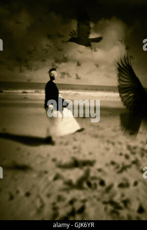 surreal image of woman wearing face mask dancing on beach and blackbirds flying - Stock Photo