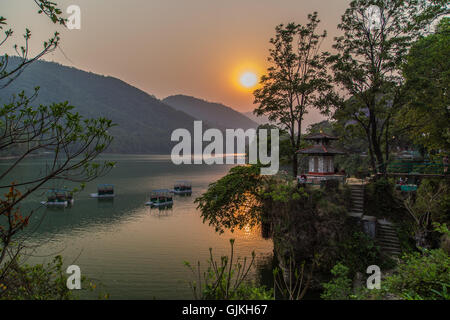 Boats on the lake in Pokhara, Nepal at sunset - Stock Photo