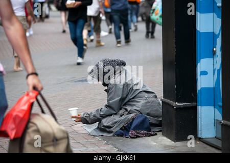 The poor beggar woman sits on the pavement. - Stock Photo