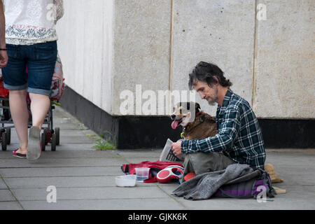 a poor man with a dog begging on the street. - Stock Photo