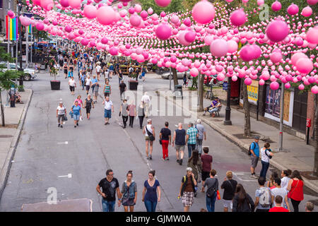 Montreal, CA - 14 August 2016: Pink balls across Rue Sainte Catherine in the Gay Village of Montreal with gay rainbow - Stock Photo