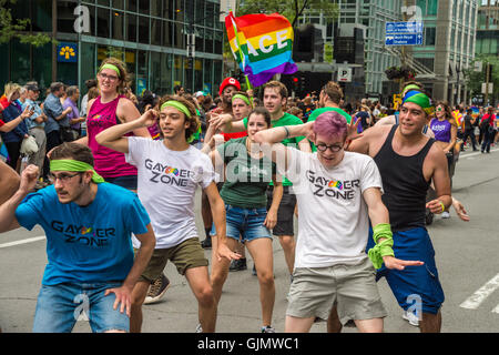 Montreal, CA - 14 August 2016: People holding gay rainbow flags take part in 2016 Gay Pride Parade - Stock Photo