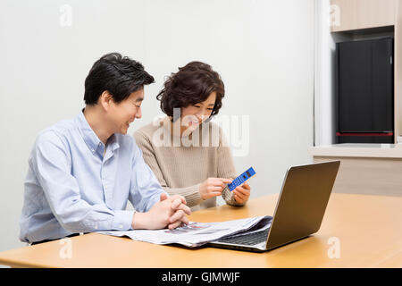 Happy Middleaged Asian Couple Reviewing Domestic Finances - Stock Photo