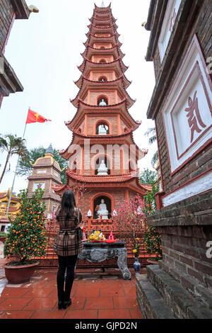 Hanoi, Vietnam - February 23, 2016: Woman praying in fron of the Tran Quoc Pagoda in Hanoi, Vietnam - Stock Photo