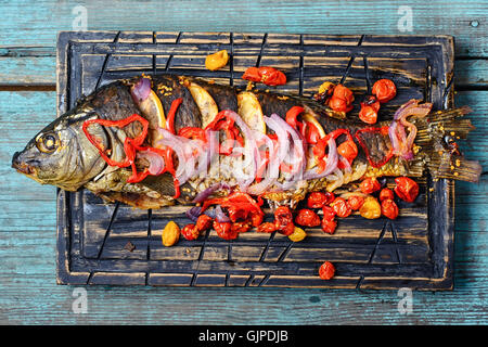 Baked fish in spices with vegetables on kitchen cutting board - Stock Photo