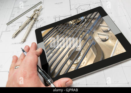 Hand of Architect on Computer Tablet Showing Kitchen Stove Details Over House Plans, Compass and Ruler. - Stock Photo