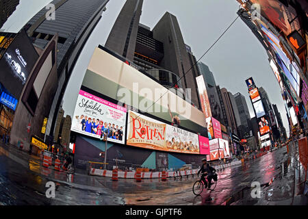 A lone biker on Broadway in Times Square ion an early weekend morning just after a rain shower. Manhattan, New York - Stock Photo