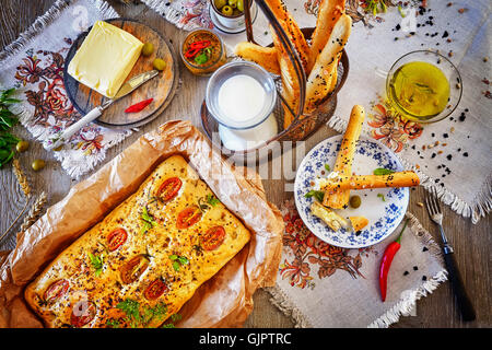 Traditional focaccia in baking paper and bread sticks, rustic setting on a wooden table from above. - Stock Photo