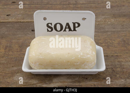 Bar of soap in vintage soap dish on rustic wood - Stock Photo