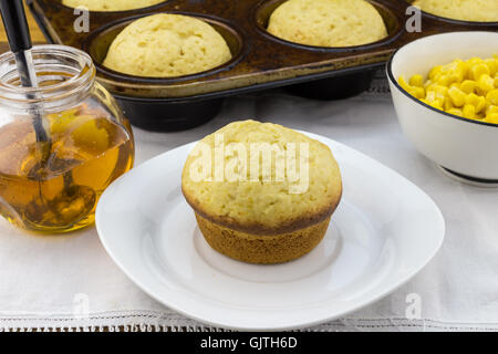 Photo of corn muffin in plate with muffins in pan, syrup and corn in a bowl on white cloth - Stock Photo