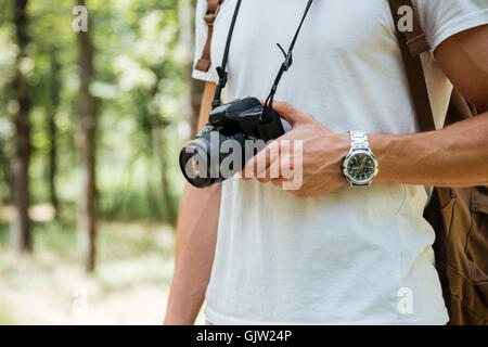 Closeup of young man photographer holding modern photo camera in forest - Stock Photo