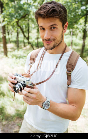 Handsome young man with backpack taking photos with old photo camera in forest - Stock Photo