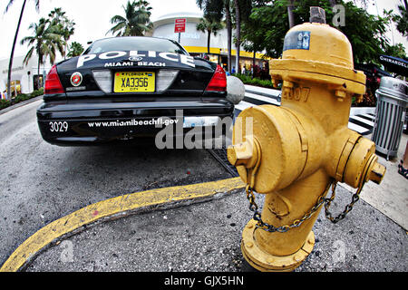 Miami Beach police cruiser parked by a yellow hydrant - Stock Photo