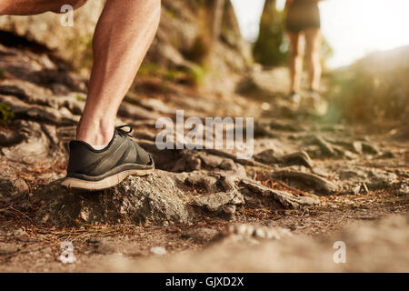 Closeup of man trail running on rocky terrain. Low section of male runner on cross country run.