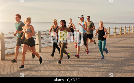 Group of runners running on urban street by the seaside. Healthy young people training together outdoors. - Stock Photo