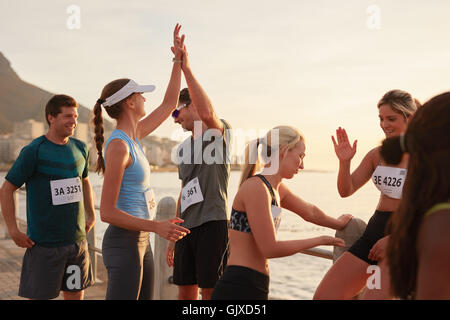 Runners giving high five to each other after a training session. Group of athletes celebrating success after a race. - Stock Photo