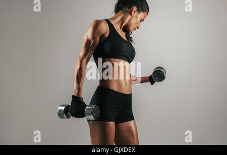 Single strong woman lifting chrome finish dumbbell weights over gray background with copy space - Stock Photo