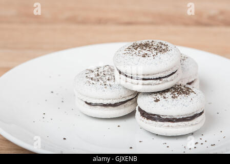 Macarons on a white plate with chocolate crumbs and filling - Stock Photo