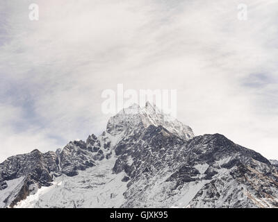 Snow covered peak of a jagged Himalayan mountain in Nepal's Everest Base Camp - Stock Photo