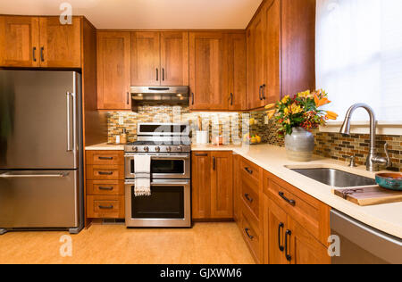Contemporary upscale home kitchen interior with cherry wood cabinets, quartz countertops, recycled linoleum floors - Stock Photo