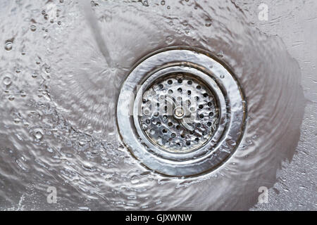 Water flowing going down drain in stainless steel kitchen sink wasting natural resources - Stock Photo