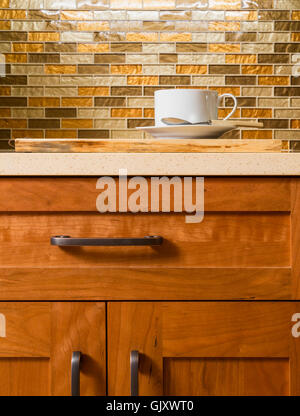High quality wood cabinets with bronze cabinet hardware & glass tile mosaic backsplash in contemporary upscale home - Stock Photo