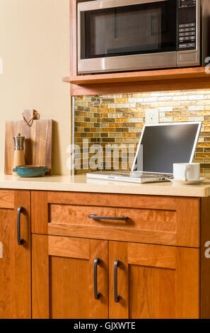 Laptop computer wireless wifi tech devices in contemporary upscale kitchen interior with wood cabinets, bronze hardware, - Stock Photo