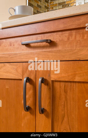 Close-up detail of high quality cherry wood cabinets with bronze cabinet hardware in contemporary upscale home kitchen - Stock Photo
