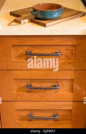 Wood cabinets with bronze cabinet hardware drawer pulls & quartz countertops in contemporary upscale home kitchen - Stock Photo