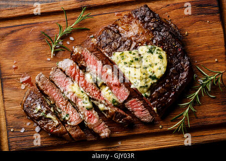 Sliced grilled Medium rare barbecue steak Ribeye with herb butter on cutting board close up - Stock Photo