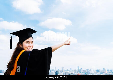 Beautiful asian university or college graduate student woman in graduation academic dress or gown, smiling and pointing - Stock Photo