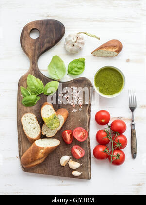 Homemade pesto sauce, fresh bread, cherry tomatoes on dark rustic wooden cutting board over white painted wooden - Stock Photo