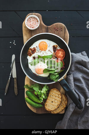 Pan of fried eggs, bacon, cherry tomatoes and fresh herbs with bread on wooden board over dark wooden background, - Stock Photo