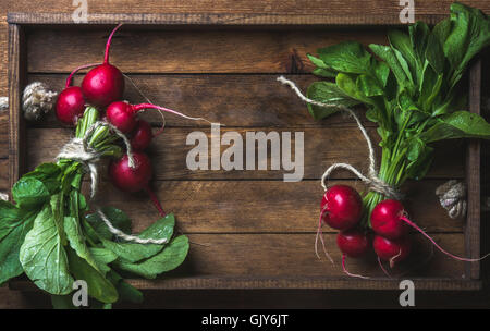 Fresh radish banches on wooden tray background. Top view, copy space, horizontal composition - Stock Photo