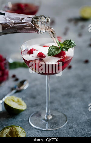 A glass of Raspberry and Pomegranate Champagne Cocktail is being topped of with champagne - Stock Photo