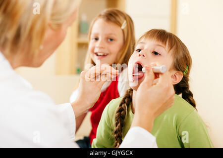 doctor examining throat of a child - Stock Photo