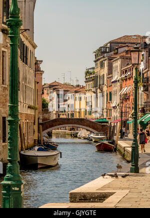 Narrow canal and arched foot bridge with traditional buildings and moored boats at both sides. Venice, Italy. - Stock Photo
