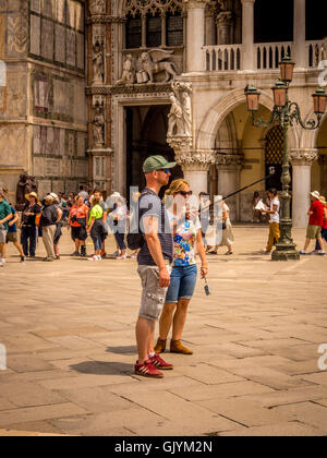 Male tourist using selfie stick to take selfie in Piazetta San Marco in Venice, Italy. - Stock Photo