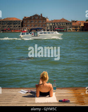 Young female reclining on a wooden jetty on the Canale della Giudecca, with a boat and the island of Giudecca in the distance. V Stock Photo
