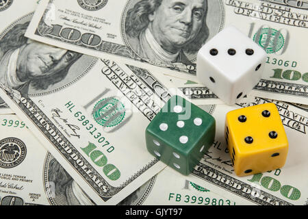 Dices of different colors on money background - Stock Photo