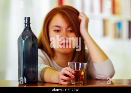 Attractive woman wearing white sweater sitting by bar counter lying over desk next to glass and bottle, drunk depressed - Stock Photo
