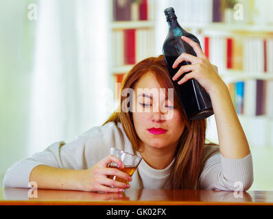 Woman wearing white sweater sitting by bar counter lying over desk holding glass and bottle to head, drunk depressed - Stock Photo