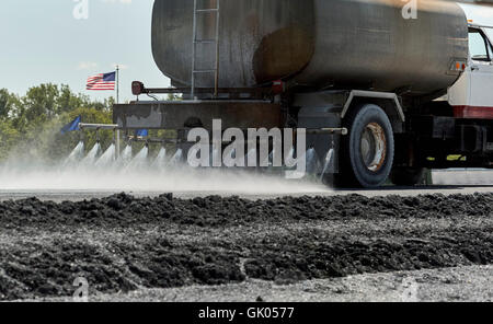 Water truck spraying water on roadway in preparation for construction - Stock Photo